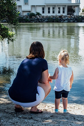 Parent and young child looking at water. Teaching you about your challenges and how to face them is part of the purpose of therapy and testing services.